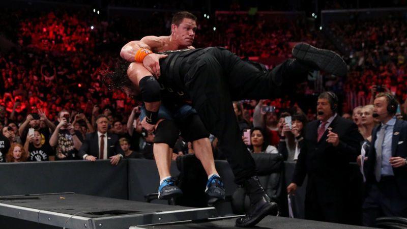 जॉन सीना को अनाउंस टेबल पर स्पीयर मारते हुए रोमन रेंस