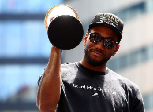 Kawhi celebrates with his Finals MVP trophy during the Raptors victory parade on Monday