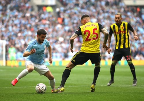 Manchester City's Silva dribbling to get pass Watford players