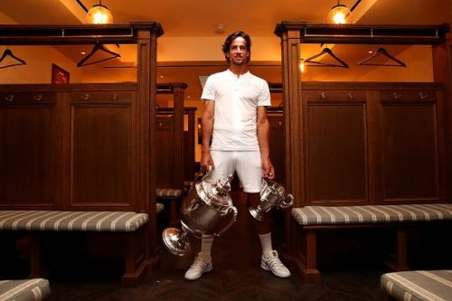 37-year-old wildcard Feliciano Lopez poses with his trophy haul: 2nd Queen's singles title and first doubles title won with Andy Murray