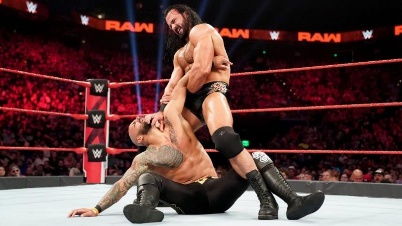 Ricochet trapped in an armbar applied by Drew McIntyre