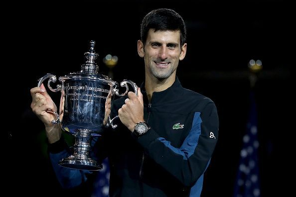 Novak Djokovic poses with his third title at the 2018 US Open