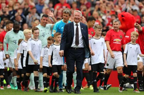 Sir Alex Ferguson with the class of '99 team in the background.