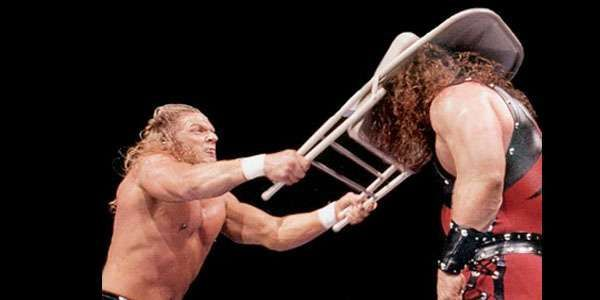 Triple H blasts a masked Kane with a steel chair