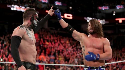Finn Balor and AJ Styles touch their doggy shaped shadow puppets together.
