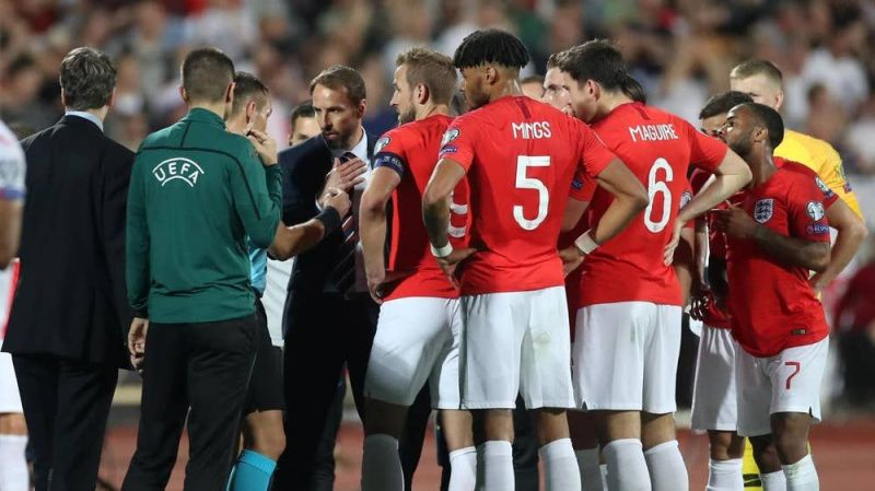 England players crowd around the match officials as racial abuse threatened to see the game abandoned