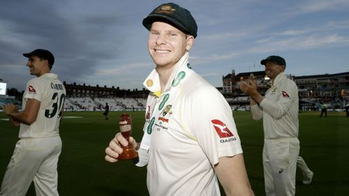 Steve Smith holds the urn as Australia celebrate retaining the Ashes after the fifth Test at The Oval.