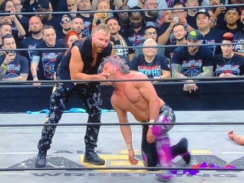 Jon Moxley attacks Kenny Omega.