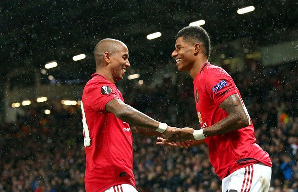 Ashley Young and Marcus Rashford celebrate under the falling snow.