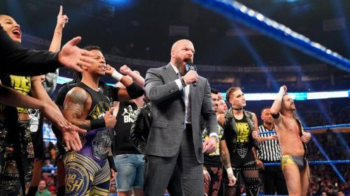 Triple H stands tall with the NXT Superstars in the middle of the ring towards the end of the show