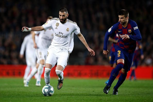 Karim Benzema tries to dribble his way past the Barca defence