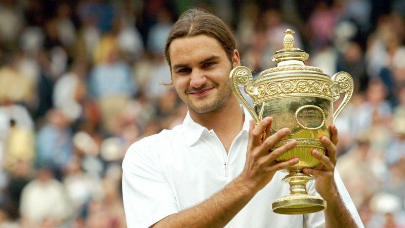 Federer hoists aloft his first Grand Slam title on the grasscourts of Wimbledon in 2003