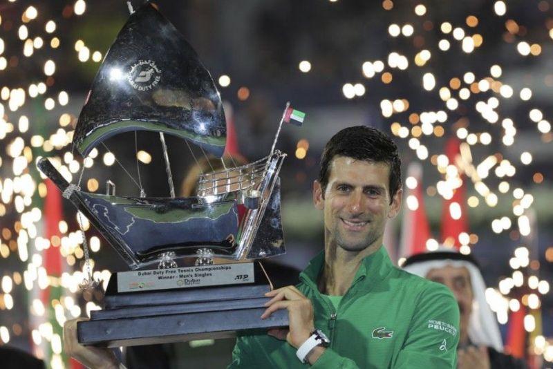 Djokovic hoists aloft his 5th Dubai Open title in 2020.