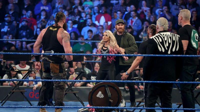 Sami Zayn using Alexa Bliss as a shield