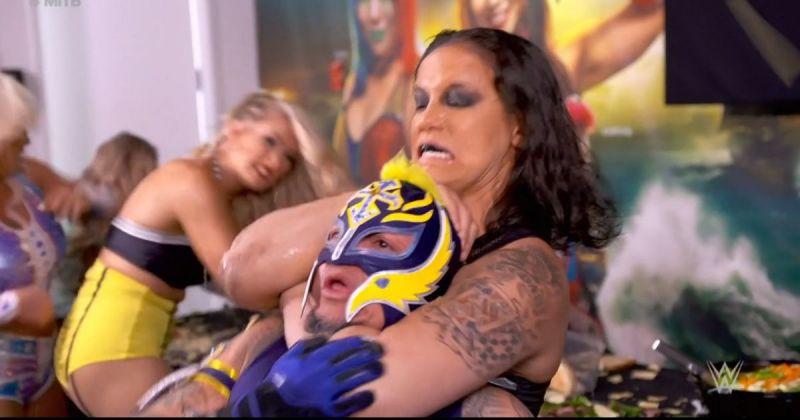 Shayna Baslzer locks Rey Mysterio in a Kirifuda Clutch.