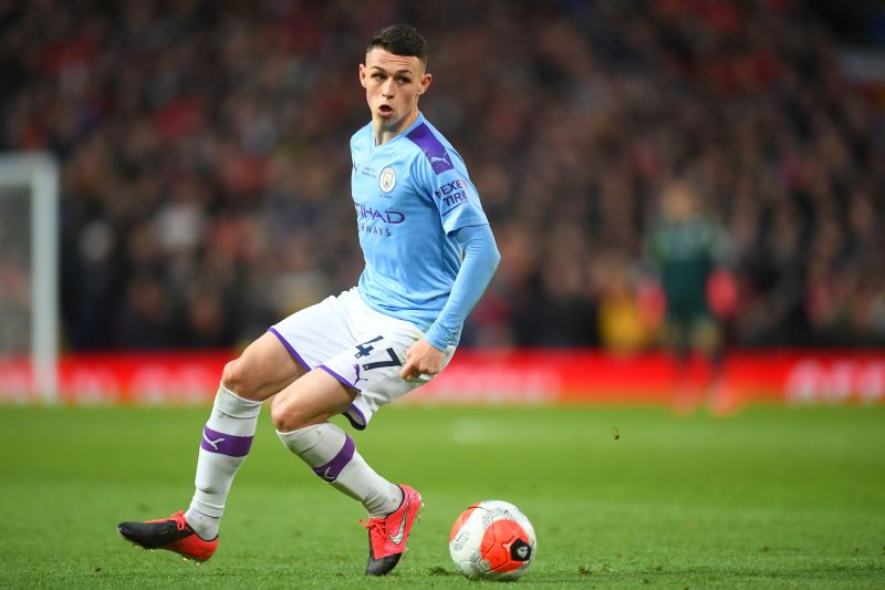 Phil Foden dribbling with the ball in recent Manchester Derby