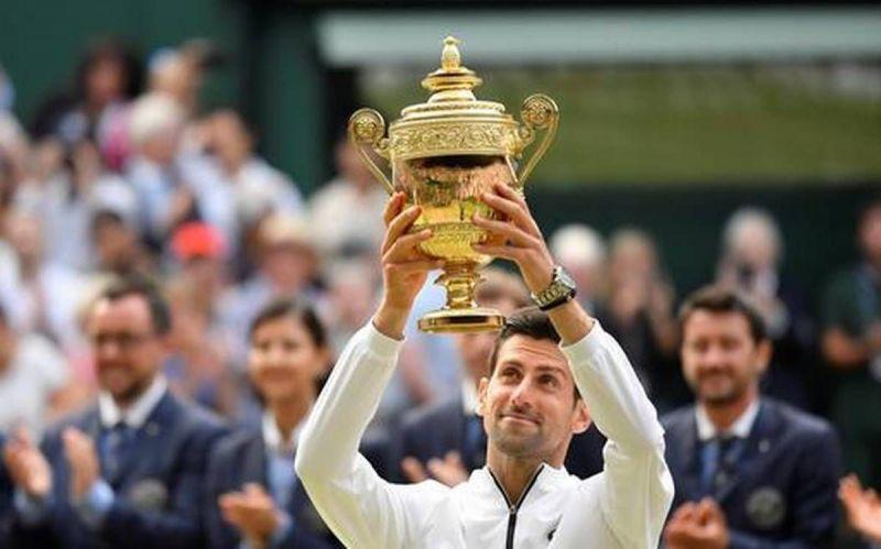 Novak Djokovic hoists aloft his fifth Wimbledon and 16th Grand Slam title in 2019