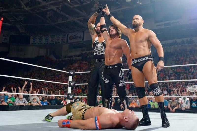 The OC (AJ Styles, Luke Gallows, and Karl Anderson) pose over a fallen John Cena in WWE