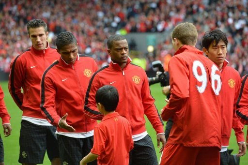 Manchester United defender Patrice Evra (3rd L) waits to shakes hands with Liverpool's Steven Gerrard (2nd right)
