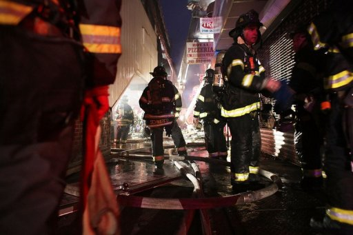 Firefighters work on an early morning storm-related fire in Brooklyn