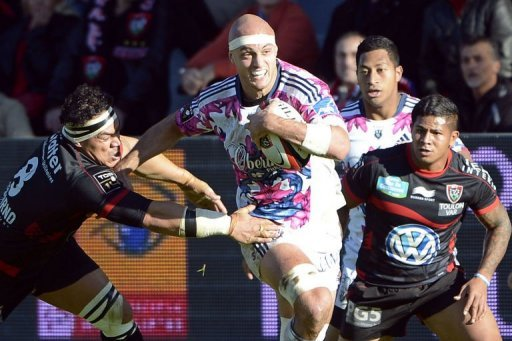 Stade Francais's Scott Lavalla (C) tries to break past RC Toulon's Number 8 Chris Masoe (L) and winger David Smith (R)