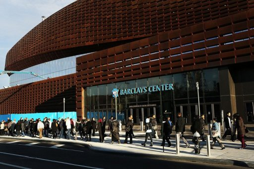 Thousands of people wait to board city buses into Manhattan at the newly opened Barclay's Center in Brooklyn