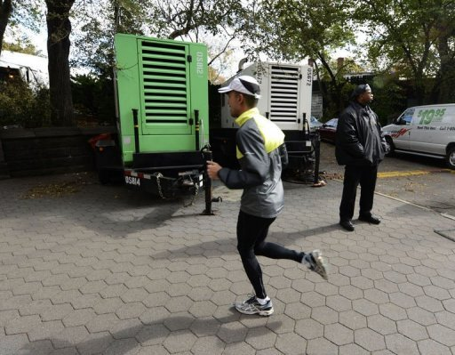 A runner passes by portable generators near the finish Line of the New York City Marathon