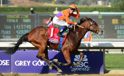 Jockey Garrett Gomez turns to look at the crowd after riding Beholder to victory