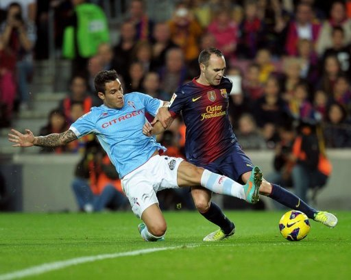 Barcelona's midfielder Andres Iniesta (R) clashes with Celta's defender Hugo Mallo