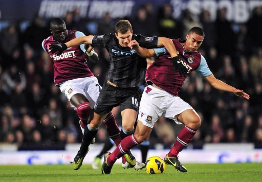 Manchester City's striker Edin Dzeko (C) clashes with West Ham's defender Winston Reid (R) and midfielder Mohamed Diame