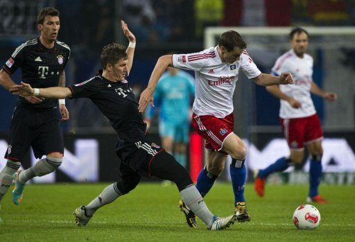 Bayern Munich's midfielder Bastian Schweinsteiger (L) and Hamburg's midfielder Marcell Jansen fight for the ball