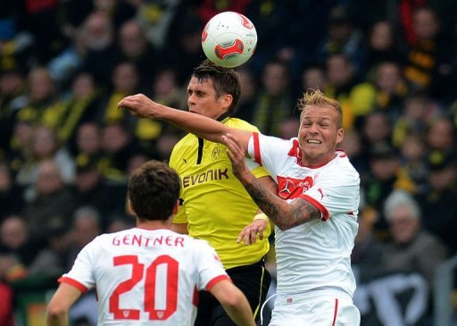 Dortmund's midfielder Sebastian Kehl (C) and Stuttgart's midfielder Raphael Holzhauser (R) jump for the ball
