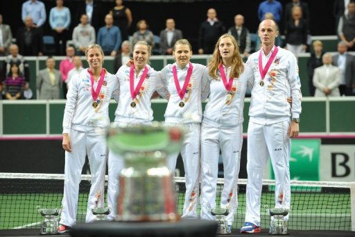 Members of Czech Republic Fed Cup team listen to the Czech anthem during the podium ceremony