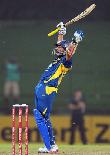 Sri Lankan cricketer Tillakaratne Dilshan raises his bat and helmet in celebration after scoring a century