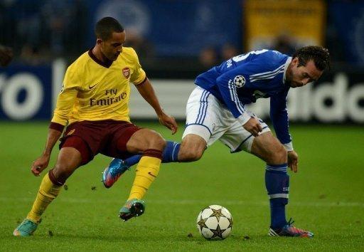 Schalke's Christian Fuchs (R) and Arsenal's Theo Walcott fight for the ball