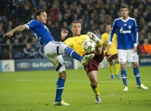 Arsenal's Lucas Podolski (C) and Schalke's Jermaine Jones (L) fight for the ball