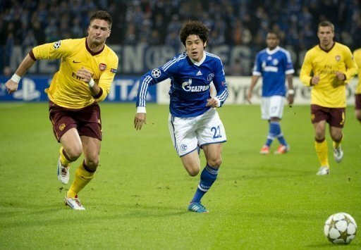 Schalke's Japanese defender Atsuto Uchida (R) vies for the ball with Arsenal's French striker Olivier Giroud