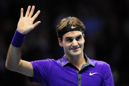 Switzerland's Roger Federer waves as he celebrates beating Spain's David Ferrer in their group B singles match in London