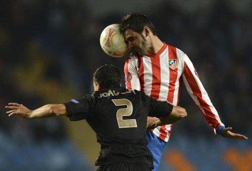 Atletico Madrid's Adrian Lopez (R) vies with Academica's Joao Dias