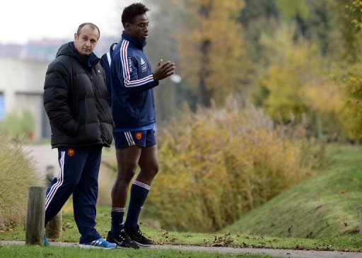 France's rugby union national team head coach Philippe Saint Andre walks with flanker Fulgence Ouedraogo (R)