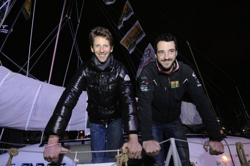 Lotus F1 Team's driver Romain Grosjean (L) and French skipper Louis Burton are seen on the monohull 'Bureau Vallee'