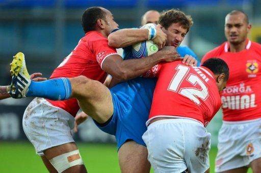 Italy centre Tommaso Benvenuti (C) is tackled by Tonga fullback Lilo Vungakoto (L) and centre Sione Piukala
