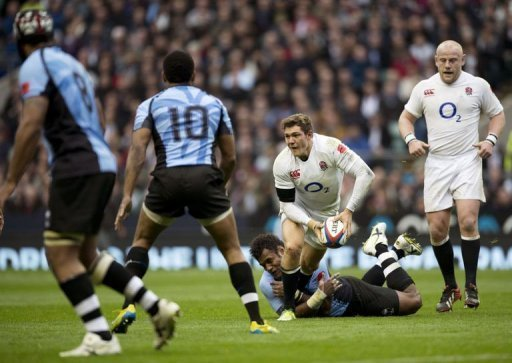 England full-back Alex Goode (C) tries to get a pass away as he gets tackled by Fiji's Sireli Naqelevuki