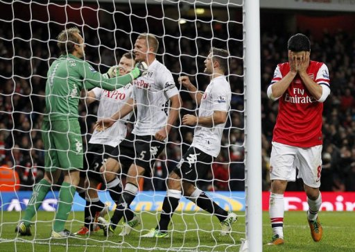 Fulham's goalkeeper Mark Schwarzer (L) celebrates saving the penalty taken by Arsenal's Mikel Arteta (R)