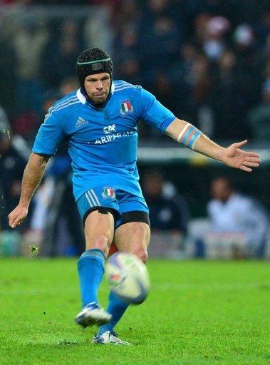 Italy's fly half Kristopher Burton kicks the ball