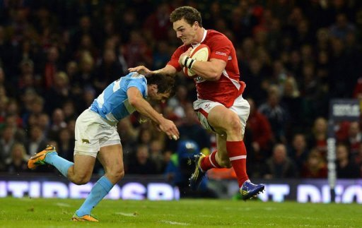 Wales' wing George North (R) hands off Argentina's wing Gonzalo Camacho