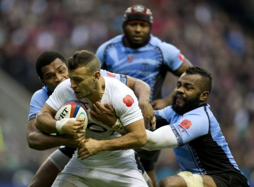 England's scrum half Danny Care (2nd L) gets tackled by Fiji's Nikola Matawalu (L) and Metuisela Talebula