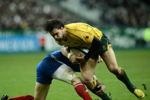 Australia's wing Adam Ashley-Cooper (R) is tackled by France's scrum half Morgan Parra