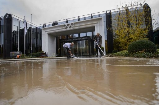 Cleaners work outside the flooded International Olympic Committee headquarters in Lausanne