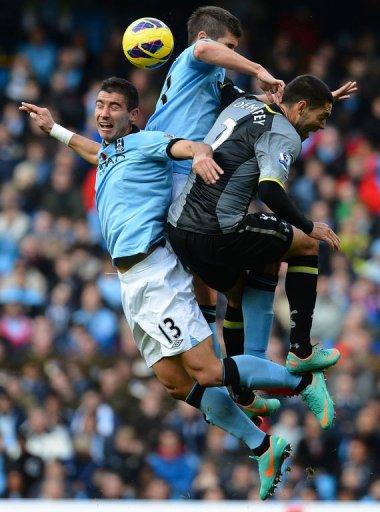Manchester City's Aleksandar Kolarov (L) and Matija Nastasic (2nd L) vie with Tottenham Hotspur's Clint Dempsey (R)
